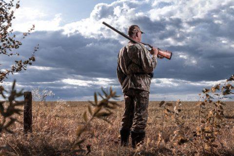 Mand står i sit jagttøj med sit jagtgevær