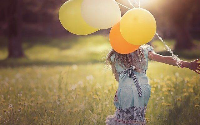 En pige med balloner løber på en græs eng